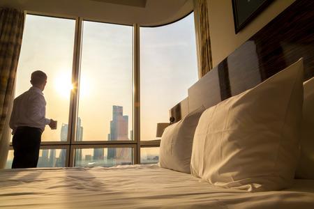 Bed maid-up met witte kussens en beddengoed in een gezellige kamer. Jonge zakenman met een kopje koffie staande op raam te kijken naar de stad landschap op de achtergrond. Focus op kussen