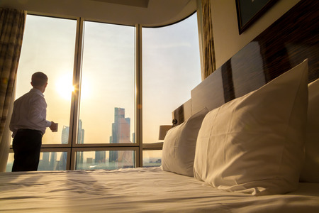 apartment: Bed maid-up with white pillows and bed sheets in cozy room. Young businessman with cup of coffee standing at window looking at city scenery on the background. Focus on cushion