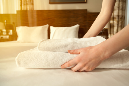 hotel staff: Close-up of hands putting stack of fresh white bath towels on the bed sheet. Room service maid cleaning hotel room. Lens flair in sunlight