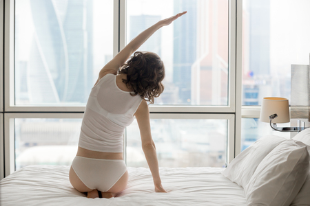 Back view of young woman doing yoga exercise at home. Female model sitting on the bed in side bending pose, working out and looking at city scenery in the window