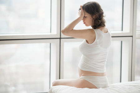 expectant arms: Profile portrait of young attractive pregnant woman sitting indoor on the bed at home touching her forehead, suffering from headache or lack of sleep on her second trimester. Copy space