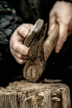 Close-up of male hands sharpening dirty old rusty axe with a grindstone on tree stump Stock Photo