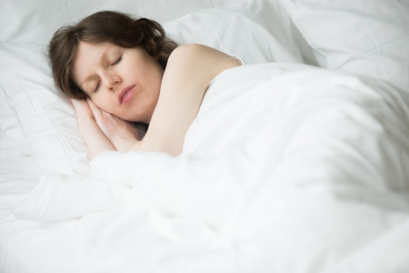 wellness sleepy: Portrait of young woman sleeping in bed. Female model relaxing in the morning at home under warm blanket