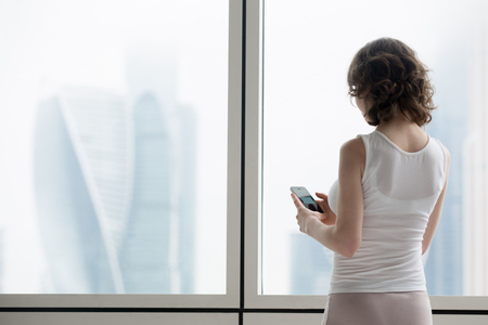 Back view of young woman making call using smartphone. Caucasian model standing at window with city scenery and looking at smart phone screen, dialing number or sending text. Copy space