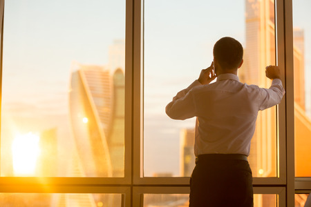 prosperous: Rear view of handsome young businessman standing in confident pose at window in his office and talking on mobile phone while looking at dawn city scenery in panoramic window. Copyspace