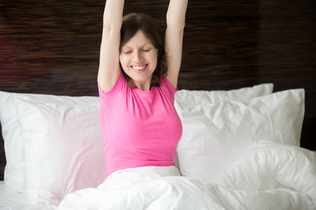 wellness sleepy: Portrait of cheerful young woman lying in bed after waking up and stretching with pleasure. Beautiful female model relaxing in the morning with closed eyes