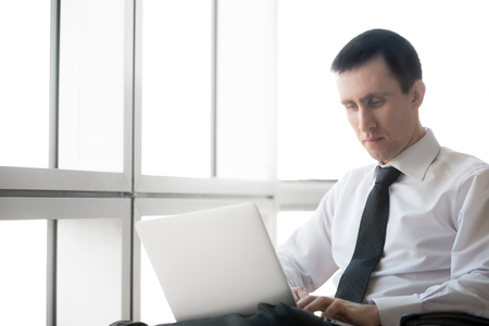 workday: Portrait of serious handsome young business man working on laptop computer. Caucasian businessperson in formal wear during his workday. Office worker focusing on work. Copy space.