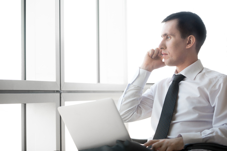 workday: Portrait of serious handsome young business man working on laptop computer and making call. Caucasian businessperson in formal wear during his workday. Office worker talking on phone. Copyspace. Stock Photo