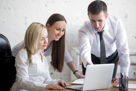 cooperativismo: concepto de trabajo en equipo. Grupo de tres jóvenes sonrientes que trabajan en proyecto en el escritorio de oficina. Equipo de negocios en el desgaste formal que usa el ordenador mientras se discute el trabajo cooperativo Foto de archivo