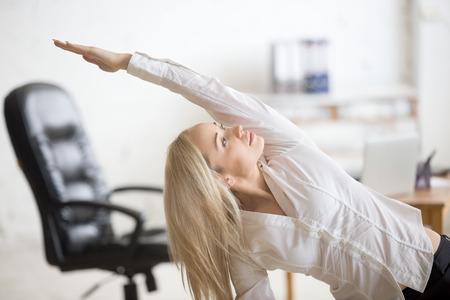 haciendo ejercicio: Concepto de negocios y estilo de vida saludable. Retrato de mujer de la oficina joven que hace ejercicio físico en el lugar de trabajo. Feliz bella dama de negocios haciendo la postura de flexión lateral sobre su tiempo de descanso