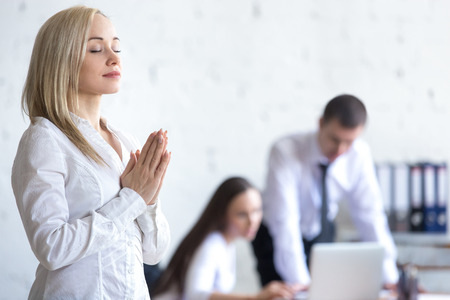 namaste: Business and healthy lifestyle concept. Beautiful young office woman meditating and relaxing with closed eyes at workplace. Attractive business lady using stress relief techniques at work. Copy space
