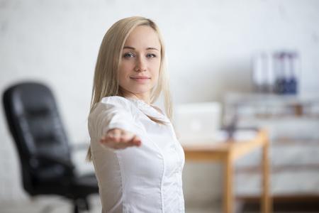 ビジネスと健康的なライフ スタイルのコンセプト。職場でヨガのポーズで立っている若い事務所女性の肖像画。幸せなビジネス女性の戦士 II 姿勢、