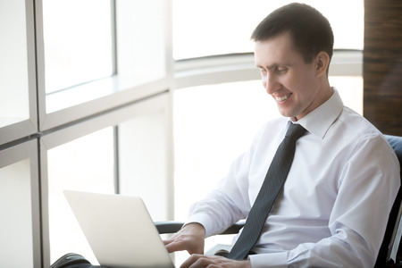 workday: Portrait of smiling handsome young business man sitting in his office and working on laptop computer. Happy Caucasian businessperson in formal wear enjoying his workday