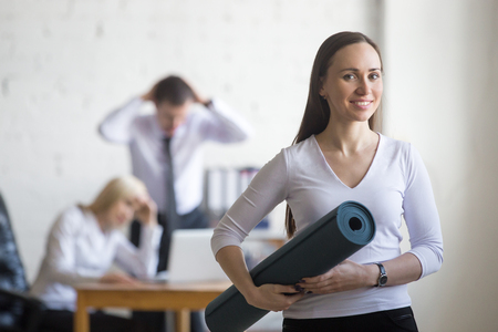Business and healthy lifestyle concept. Portrait of beautiful sporty calm young office woman standing with yoga mat at workplace on break time while her stressed colleagues working on the background