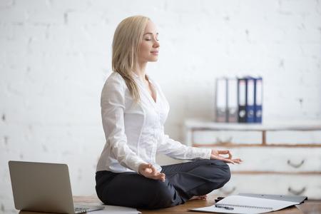 mujer meditando: Concepto de negocios y estilo de vida saludable. Retrato de mujer de la oficina joven sentado con las piernas cruzadas en la mitad de la yoga posición de loto en el lugar de trabajo. La señora sonriente de negocios meditando después de terminar su trabajo Foto de archivo