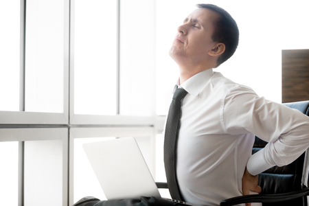 Handsome young stressed businessman sitting in his office using laptop. Caucasian businessperson suffering from backache after working on pc, holding his waist with pained expression, feeling pain, touching his aching back