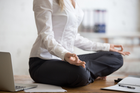Business and healthy lifestyle concept. Young yogi office woman sitting cross-legged in half lotus yoga pose at workplace. Smart casual business lady meditating on her break time. Close-up