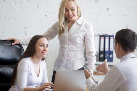 cooperativismo: concepto de trabajo en equipo. Grupo de tres sonriente jóvenes atractivas que trabajan en proyecto en el escritorio de oficina. Equipo de negocios en el desgaste formal que discute el trabajo cooperativo en la reunión de la oficina