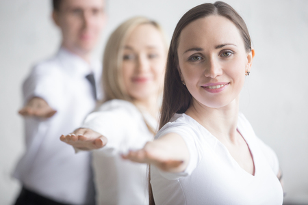 Business and healthy lifestyle concept. Portrait of young office workers standing in yoga pose at workplace. Smiling business people doing Warrior II posture, Virabhadrasana 2 pose on break time Stock Photo