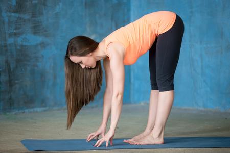 ardha: Portrait of beautiful young woman enjoying yoga indoors. Ardha Uttanasana (Intense Stretch, Standing Half Forward Bend pose).