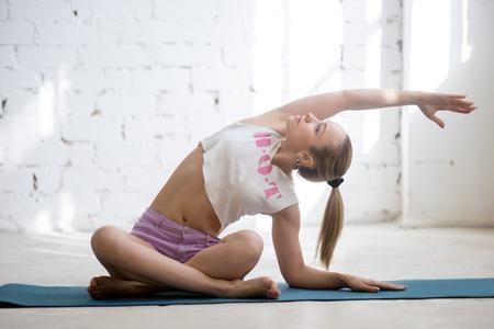sukhasana: Portrait of beautiful young woman wearing casual clothing doing yoga exercise indoors. Sitting in variation of Easy Posture, Sukhasana.