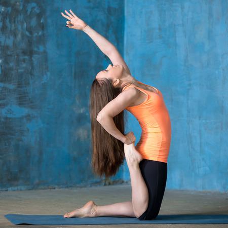 pada: Beautiful young woman dressed in bright sportswear enjoying yoga indoors. Doing One-legged Camel Posture. Stock Photo