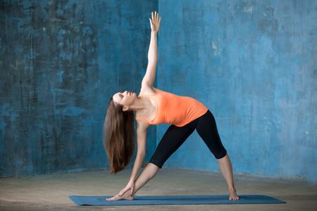 trikonasana: Beautiful young woman dressed in bright sportswear enjoying yoga indoors. Doing Extended Triangle pose, Utthita Trikonasana. Full length Stock Photo