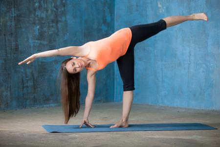 chandrasana: Beautiful young woman dressed in bright sportswear enjoying yoga indoors. Ardha Chandrasana posture, Half Moon Pose.