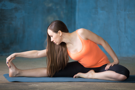 janu: Beautiful young woman dressed in bright sportswear enjoying yoga indoors. Seated Floor Hamstring Stretch or Head-to-Knee Forward Bend Pose