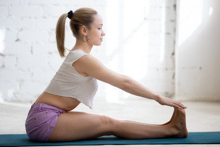 to bend: Beautiful young woman wearing casual clothing doing yoga indoors. Sitting in Paschimottanasana, Seated Forward Bend Pose.
