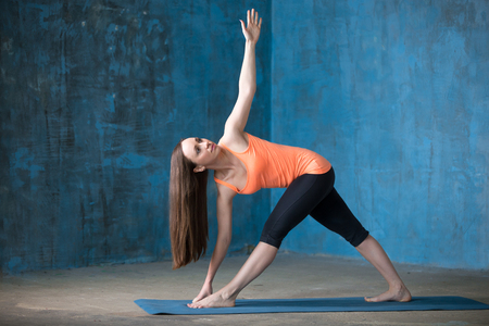 trikonasana: Yogi girl working out in grunge interior with blue wall. Revolved Triangle Pose, Parivrrta Trikonasana. Full length Stock Photo