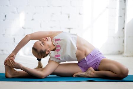 adentro y afuera: Muchacha de la yogui de trabajo en el interior de loft soleado. Sentado en Parivrtta Ener Sirsasana, de revolución de cabeza a la rodilla flexión hacia delante Pose. Longitud total
