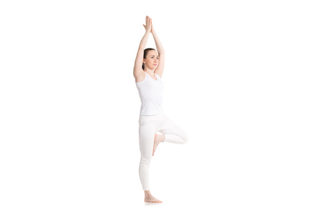anjali: Sporty attractive young woman in white sportswear doing yoga Tree pose, hands above the head in Anjali mudra
