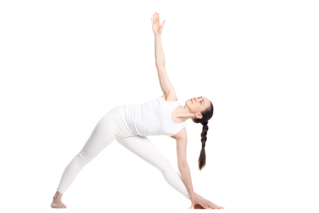 utthita: Sporty beautiful smiling young woman standing in Utthita Trikonasana, Extended Triangle Pose