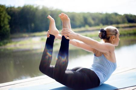 Bella sportivo in forma giovane donna bionda in abbigliamento sportivo lavorando all'aperto nel parco sul lago, facendo esercizi Backbend