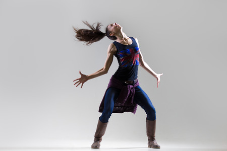 Stylish dancing young woman portrait. Fit girl wearing English flag tank top warming up, working out. Dancer shaking head in excitement with her long ponytail flying. Studio image. Grey background Stock Photo
