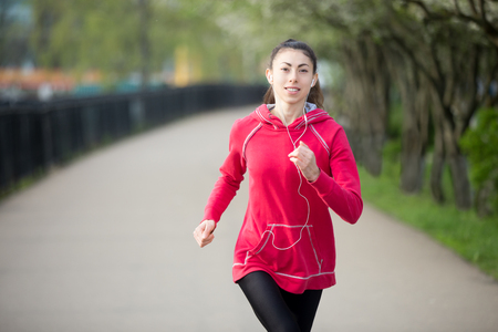 active listening: Portrait of smiling beautiful female running in park during everyday practice. Fitness woman jogging outdoors and listening music. Sport active lifestyle concept. Stock Photo