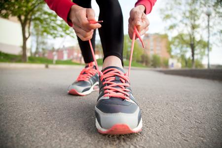 스포티 한 여자는 연습 전에 신발을 실행에 신발 끈을 매는. 야외에서 조깅을 준비하는 여성 선수. 러너 훈련을위한 준비. 스포츠 활동적인 생활 개념