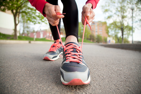 'getting ready': Sporty woman tying shoelace on running shoes before practice. Female athlete preparing for jogging outdoors. Runner getting ready for training. Sport active lifestyle concept. Close-up