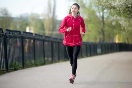 escucha activa: Retrato de la sonrisa hermosa mujer corriendo en el parque durante la pr�ctica cotidiana. Fitness mujer corriendo al aire libre y escuchar m�sica. Concepto de deporte de estilo de vida activo. Longitud total