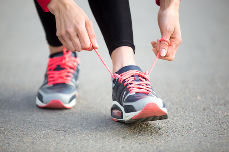jogging shoes: Female hands tying shoelace on running shoes before practice. Woman athlete preparing for jogging outdoors. Runner getting ready for training. Sport active lifestyle concept. Close-up