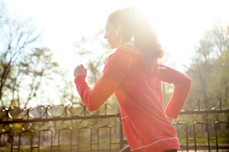active listening: Portrait of happy beautiful female running in park during everyday practice. Woman athlete jogging outdoors and listening music. Sport active lifestyle concept. Lens flair from warm sunlight Stock Photo