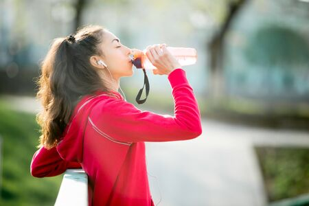 water sport: Profile portrait of sporty woman drinking in park after jogging. Female athlete runner getting ready for running routine. Fit girl listening music and enjoying drink with closed eyes outdoors Stock Photo
