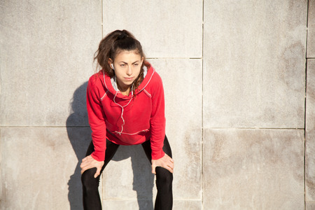 active listening: Portrait of young beautiful female leaning on gray wall while resting after everyday practice. Woman athlete jogger taking a break and listening music. Sport active lifestyle concept. Copy space