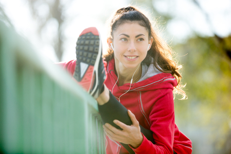 hamstring: Portrait of sporty smiling woman doing hamstring stretch in park after jogging. Female athlete runner getting ready for running on the bridge. Fit girl enjoying workout. Active lifestyle concept Stock Photo