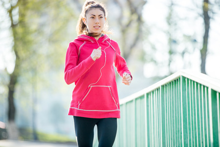 escucha activa: Portrait of smiling beautiful female model running on the bridge during everyday practice. Fit resolute woman jogging outdoors and listening music. Sport active lifestyle concept