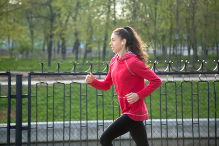 active listening: Portrait of happy beautiful female running in park during everyday practice. Woman athlete jogging outdoors and listening music with earphones. Sport active lifestyle concept