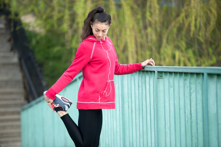 escucha activa: Portrait of sporty woman doing stretching exercises in park before training. Female athlete runner listening music while getting ready for running routine on the bridge. Sport active lifestyle concept