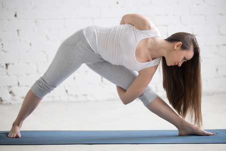 utthita: Attractive young woman working out indoors. Beautiful model doing exercises on blue mat in room with white walls. Variation of Utthita Trikonasana with hands crossed behind back. Full length Stock Photo