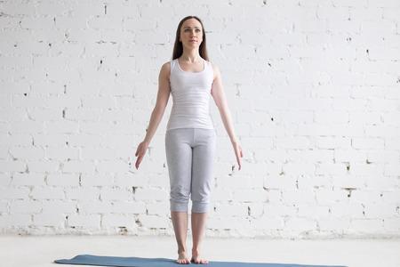 실내에서 일하는 매력적인 행복 젊은 여자. 블루 매트에 요가 운동을 하 고 아름 다운 모델의 전면 뷰 초상화. Tadasana, 산 포즈에 서 서. 전체 길이